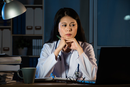 白い医療ガウンのあごに手を維持して考えて夜遅くの美しい若い医者のフロント ビュー。混血アジア中国の女性モデル。医療と健康の概念