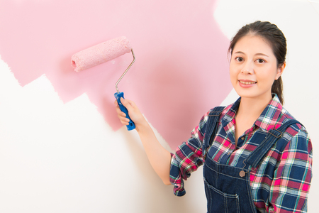 housepainter: Happy beautiful young woman doing wall painting. multicultural asian chinese girl model