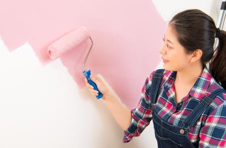 壁の絵をやって幸せな美しい若い女性。多文化共生のアジア中国の女の子モデル