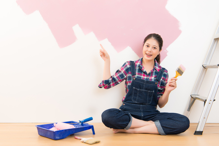 Woman with paintbrush in hand and pointing presenting accessories sitting next to a ladder. Multiethnic Asian girl model Imagens