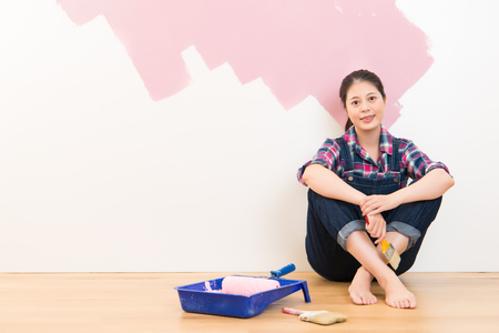 redecorating: Laughing woman painting her wall in pink and looking at camera. Multiethnic Asian girl model