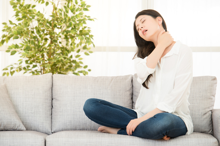 Young woman sitting on sofa with neck pain at home. lifestyle and health concept. mixed race asian chinese model.