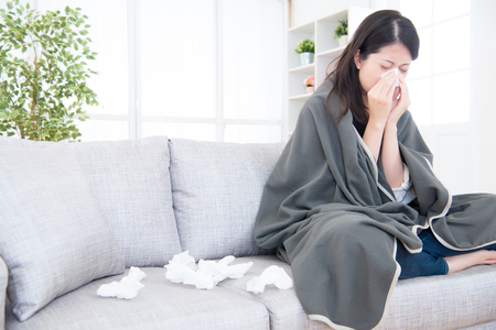 Sick young woman sneeze at home on the sofa with a cold, she is covering with a blanket and blowing her nose. medical and health concept. mixed race asian chinese model