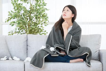アレルギー反応を伴う病気の女性。女性キャッチ寒さとインフルエンザ、喉の痛みを感じる。医療と健康の概念。混血アジア中国モデル