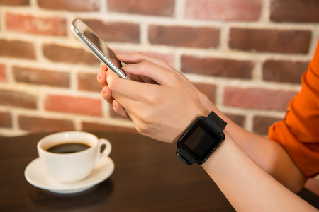 retro woman: Woman wearing smart watch on hand, holding mobile phone, cup of coffee on light wooden table. mixed race asian chinese model