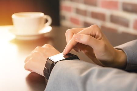 tarde de cafe: In coffee bar a woman using her smartwatch and drinking coffee. Close-up hands. mixed race asian chinese model.