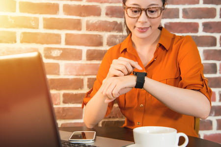 Womans hands touching smart watch on hand and mobile phone, cup of coffee on wooden table at cafe. mixed race asian chinese model Stock Photo