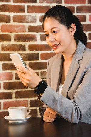 syncing: Good looking young business manager syncing her smart watch with her smart phone while working on a business trip. mixed race asian chinese model.
