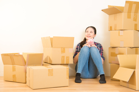 Smiling young woman caressing her piggy bank with a look of anticipation as she kneels amongst cardboard cartons in her new home imagining her new decor. mixed race asian chinese model