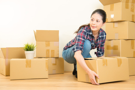 domicile: Woman holding cardboard box with things for moving into new house. mixed race asian chinese model