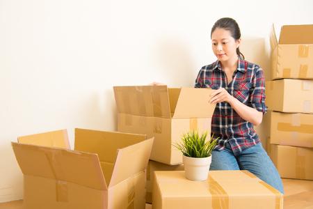 魅力的な若い女性は動いて、段ボール箱の中に立っています。混血アジア中国モデル