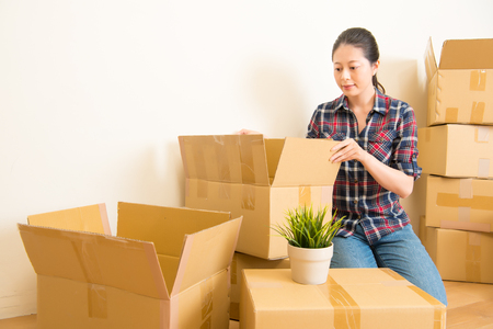 Attractive young woman is moving, standing among cardboard boxes. mixed race asian chinese model Stok Fotoğraf - 76697298