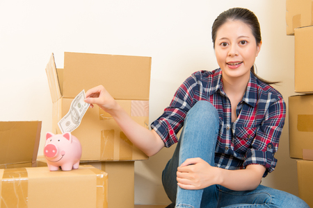 beautiful woman between transport boxes put money cash in piggy bank in her hands. mixed race asian chinese model