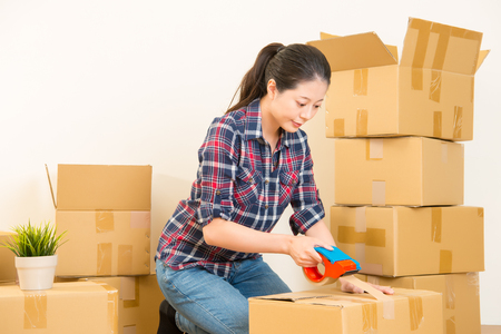 Woman moving into new home and unpacking carton boxes. mixed race asian chinese model