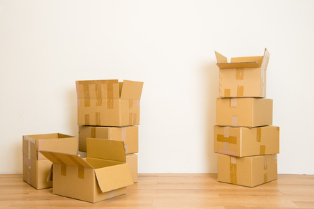 Moving in Stack of cardboard boxes in the empty room with copy space in apartment