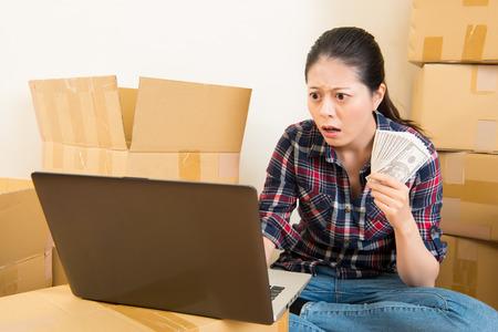 心配し、家賃についてショックを受けた女性を高める家具を買うお金が足りない。混血アジア中国モデル。 写真素材