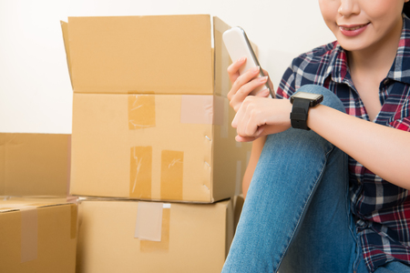 woman using smartphone connecting smart watch sitting around carton boxes after moving house. mixed race asian chinese model. Stock Photo