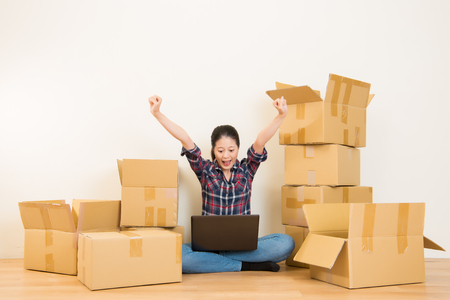 Concetto di casa mobile - donna eccitata rilassarsi sul pavimento ricerca sul computer e festeggiare in nuova casa. Razza mista razza cinese modello. Archivio Fotografico - 76794420