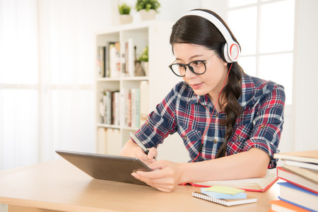 행복 한 학생 줄에 학습 및 집에서 책상 패드 화면을보고 숙제를 하 고 디지털 태블릿에 노트. 혼합 된 경주 아시아 중국 모델입니다.