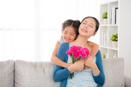 chinese mother sitting on the sofa in the living room little daughter giving her hug from behind and sent to mother's day carnations bouquets and happy together celebrate festival with copyspace. Foto de archivo