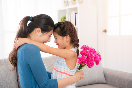 beautiful mother hug with cute little daughter and look each other holding pink bouquet in living room to celebrate the mothers day at home on sofa.