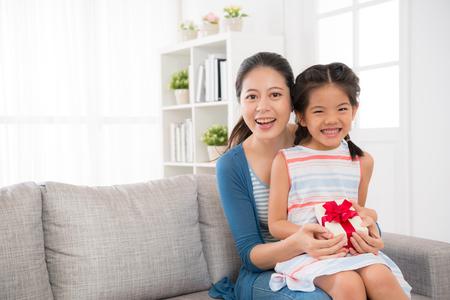 행복 한 여자 자녀와 어머니 거실에서 소파에 앉아 어머니의 하루 선물을 잡고 copysapce와 함께 특별 한 휴일을 기념하기 위해 함께 웃 고 카메라를 얼굴. 스톡 콘텐츠 - 77187586