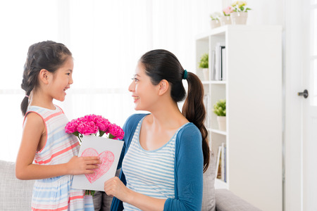 smiling asian little girl prepare a pink carnation bouquet and love card giving gift for beautiful mother at mothers day at home in the living room sofa looking each other with copyspace.