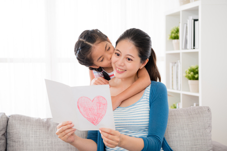 cute little daughter kiss the womans cheek when the mother received the love card gift and reading happily sitting on the sofa in the living room in mothers day at home.