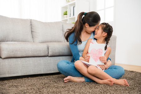 happy mom holding happy little daughter and giving her kiss sitting on the living room floor when she knowing girl prepare mother's day card gift. Archivio Fotografico