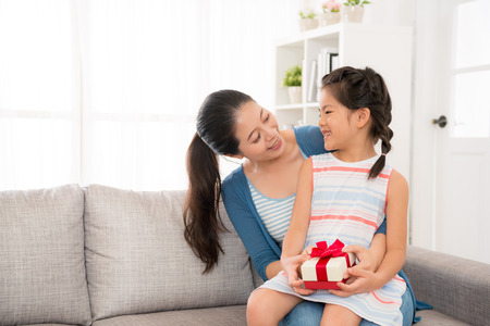 happy asian mother sitting on the couch holding the smiling daughter expression of thanks when she receives the mother s day gift in the living room from the sweet girl with copyspace. Stock fotó