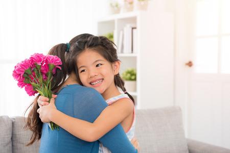 그녀는 아이가 그녀의 카네이션 꽃다발 copyspace 통해 어머니의 날 선물로 준 알면서 거실에 집에서 그녀의 포옹을주는 사랑스러운 작은 딸을 들고 젊은 주부. 스톡 콘텐츠 - 77187604