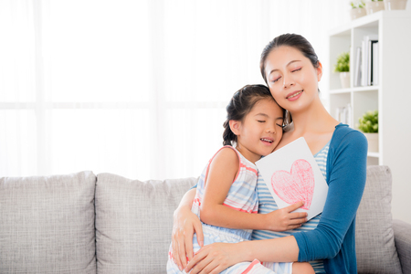 beautiful mom holding lovely little daughter hug sitting together on living room sofa when she receives love card gift happy to enjoy mother's day holiday at home.