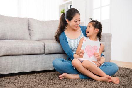 cute little girl prepared mothers day card ready give young woman when sitting on the living room floor together and looking at each other.