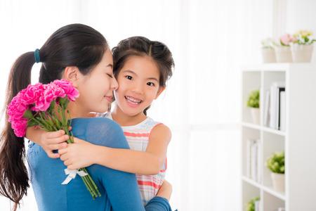 Abrazo de papá joven asiático con la niña pequeña , ella se ha divirtiendo a su hija que lleva sus rosas rosadas se besan para el día de fiesta juntos juntos en la noche juntos con el saludo Foto de archivo - 77187648