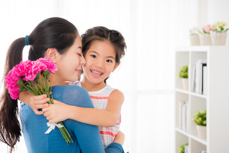 asian young mother embrace with smiling little girl when she knowing that her daughter was preparing pink carnations bouquets for mothers day gift standing in the living together with copyspace.