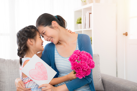 young asian mother accept the little daughter hand painted card embrace holding a pink flower girl sitting on the sofa in the living room happy looking at each other with copy space at mother's day.