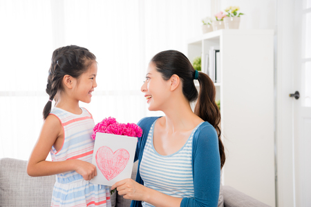 asian chinese mother and daughter look at each other sitting on the couch sofa and holding bouquets and card gift together in mothers day with blank copyspace.