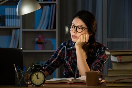 Onderzoeken laat in de nacht laat opblijven. De jonge, uitgeputte geconcentreerde student voelt zich slaperig aan het bureau in haar kamer in het donker bij de lamp. gemengd ras Aziatisch Chinees model. Stockfoto - 77187911