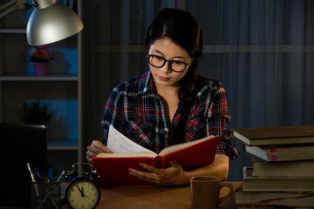 젊은 학생 집에서 책상 독서도 서의 더미와 함께 공부 하 고 커피 잔 대학 시험을 준비 흐린 빛에서 교육 개념. 혼합 된 경주 아시아 중국 모델입니다.