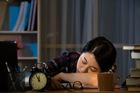 夜遅く疲れている留学生、彼らはデスクトップに眠っているし、本の山に傾いた。混血アジア中国モデル。 写真素材