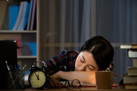 늦은 밤에 공부하는 피곤한 학생들은 책상 위에서 자고 책 더미에 기대고 있습니다. 혼합 된 경주 아시아 중국 모델입니다. 스톡 콘텐츠