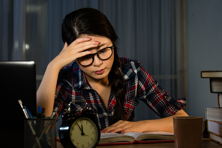 Student having a terrible headache while learning at home. Young woman having deadline. mixed race asian chinese model. Stock Photo