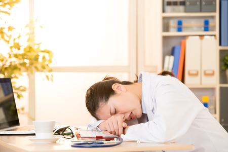 여자 의사 고통스러운 고통 머리 얼굴 누워 병원에서 병원에서 책상에 누워. 혼합 된 경주 아시아 중국 모델입니다. 의료 및 건강 관리 개념입니다.