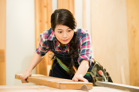 Concentrated young female carpenter cutting wood with table saw in her workshop studio. mixed race asian chinese model.