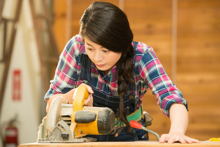 carpenter using circular Saw. female woodworker holding circular table electric saw cutting wood in workshop. mixed race asian chinese model