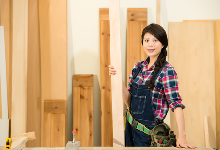 woman handle success: successful carpenter face looking at camera holding wood board standing in workshop. mixed race asian chinese model.