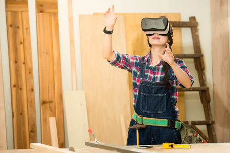 Man doing woodwork in carpentry. Carpenter work on wood plank with vr headset device in workshop. mixed race asian chinese model.