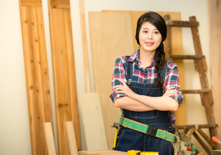 female carpenter doing her job in carpentry workshop, while working and standing in her workshop studio. mixed race asian chinese model. Фото со стока