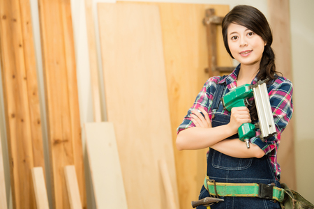 wooden carpenter face looking at camera holding air compressor nail gun standing in workshop. mixed race asian chinese model.