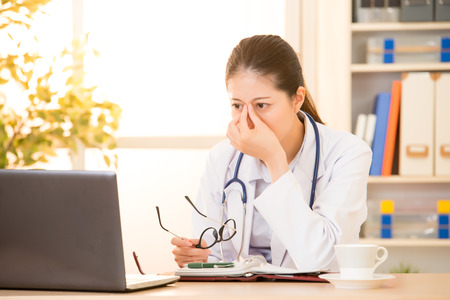 Feeling tired and stressed. Frustrated young woman doctor keeping eyes closed and massaging nose while sitting in clinic at hospital. mixed race asian chinese model.